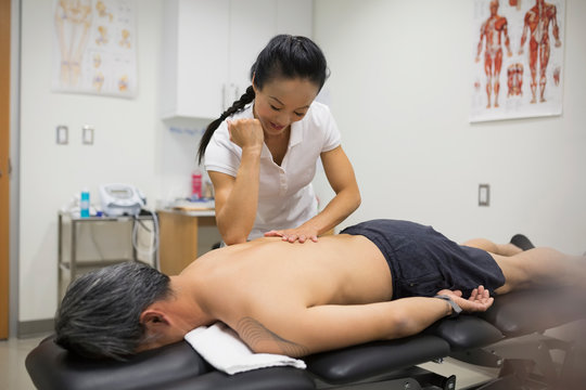 Physical therapist using elbow to massage patient back
