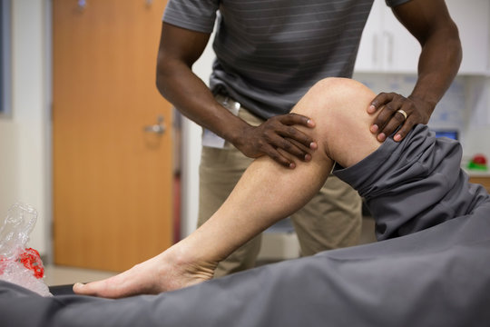 Physical therapist stretching patient knee