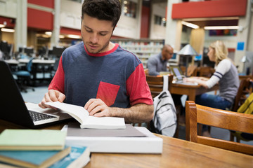 College student studying with book and laptop library