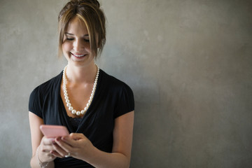 Businesswoman texting with cell phone against gray background