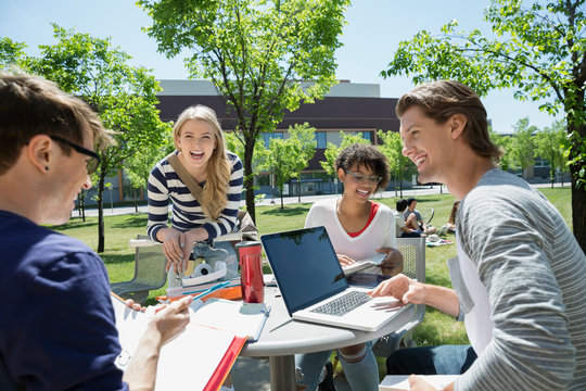 Laughing college students studying table on sunny campus