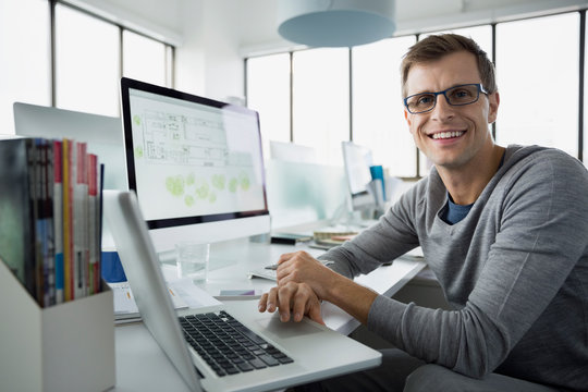 Portrait smiling architect working at laptop and computer