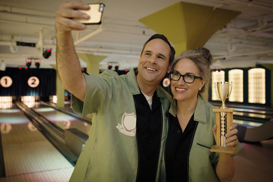 Smiling couple bowling shirts taking selfie with trophy