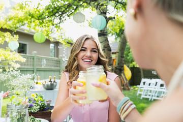 Smiling women toasting lemonade jars at garden party