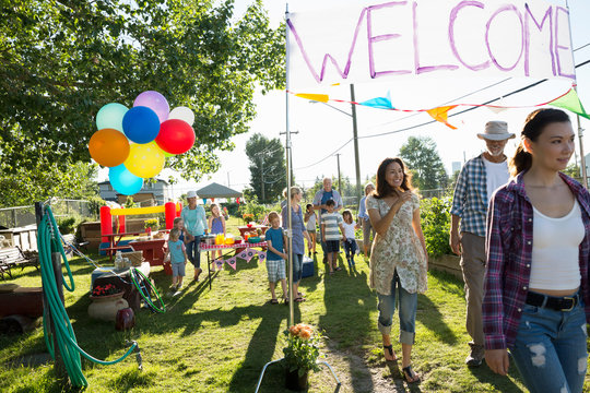 Neighbors walking under Welcome sign party in park