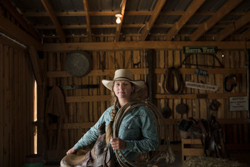 Portrait confident female rancher saddle and rope stable