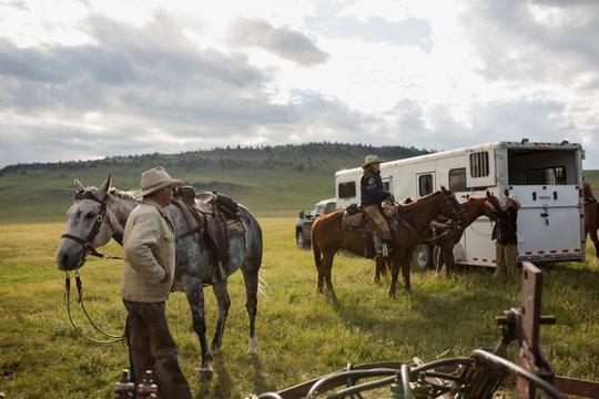 Ranchers preparing horses outside horse trailer in field