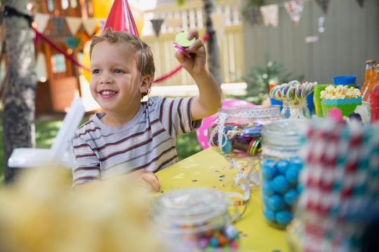 Boy wearing birthday party hat holding candy