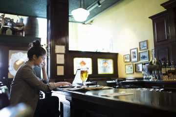 Businesswoman working at laptop in pub
