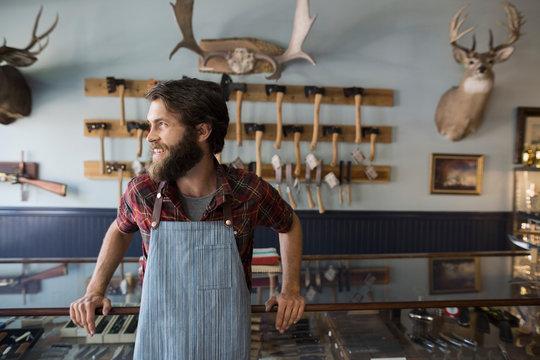 Smiling bearded shop worker looking away