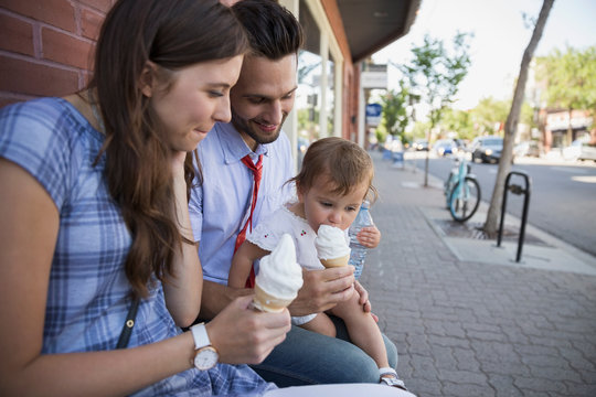 Family eating soft serve ice cream on sidewalk