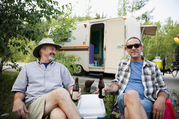 Father and son drinking beer campsite outside camper