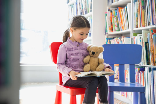 Girl with teddy bear reading book in bookstore