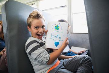 Portrait enthusiastic schoolboy showing earth drawing school bus