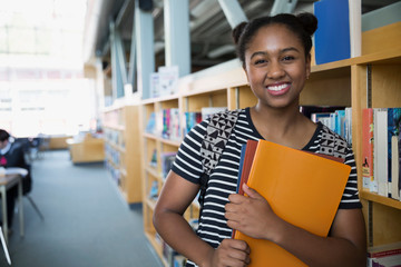 Portrait confident high school student in library