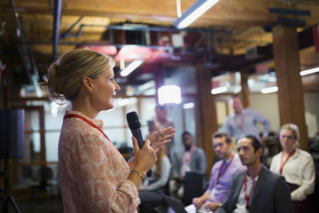 Businesswoman with microphone speaking to conference audience
