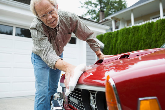 Senior man waxing classic car in driveway
