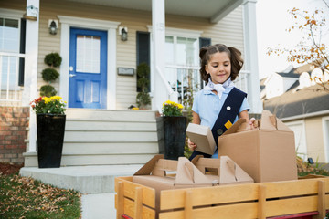 Girl scout with wagon selling cookies in neighborhood
