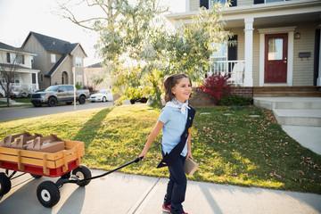 Girl scout pulling wagon selling cookies in neighborhood