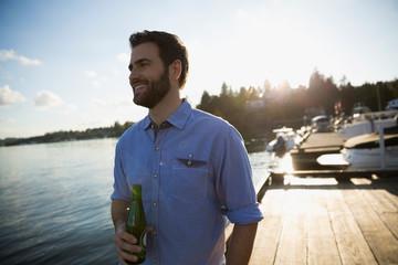 Smiling man drinking beer on lake dock