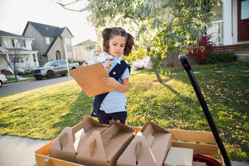 Girl scout with clipboard checking cookies in wagon