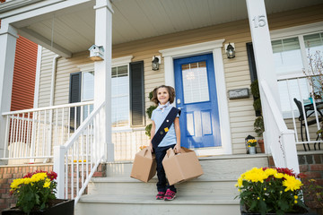 Girl scout with cookies on front stoop
