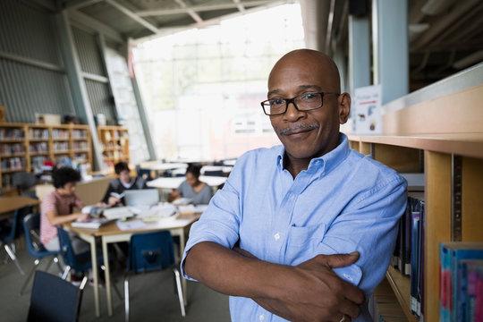 Portrait confident high school teacher in library