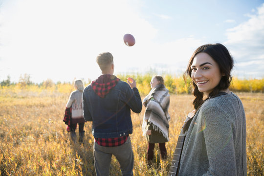 Portrait smiling young woman with friends in sunny field