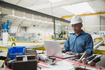 Worker at laptop in manufacturing plant