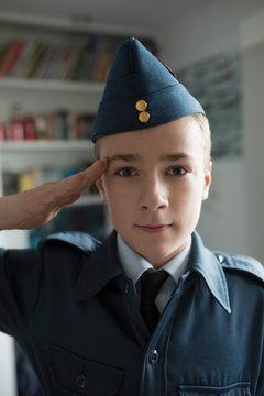 Portrait boy saluting in cadet uniform