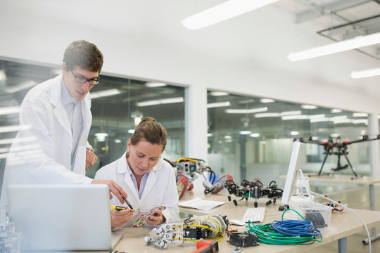 Engineers at laptop assembling robotics in factory