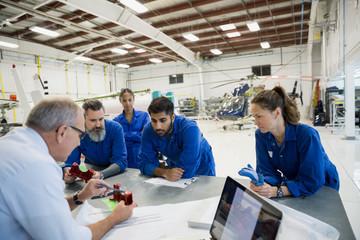Manager explaining part to mechanics in airplane hangar