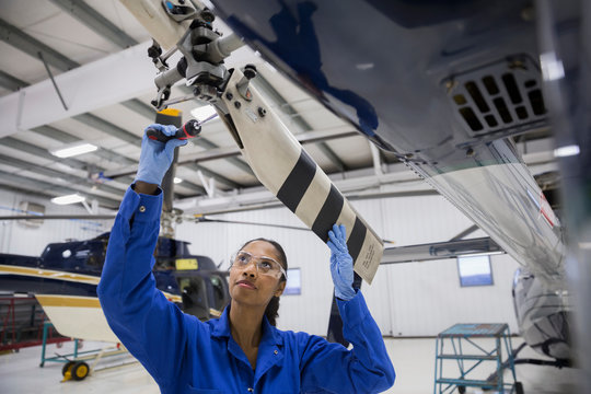 Female helicopter mechanic repairing propellor in airplane hangar