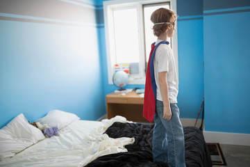 Boy superhero cape and mask standing bed
