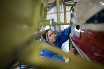 Mechanic examining helicopter in airplane hangar