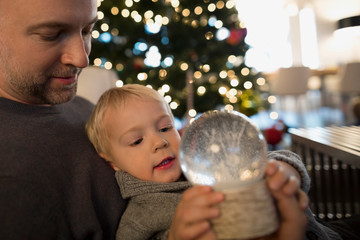 Father holding son with snow globe
