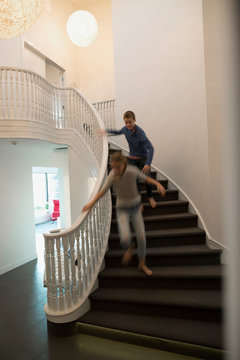 Brother chasing sister down foyer staircase