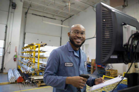 Smiling worker with clipboard at computer in factory