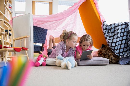 Girls using digital tablet inside living room fort