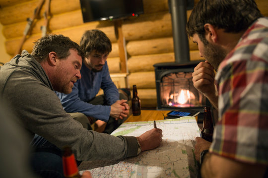 Men drinking beer and mapping adventure in cabin