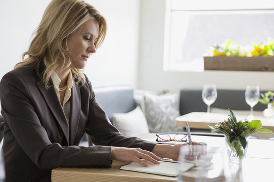 Businesswoman writing in notebook at table in bistro