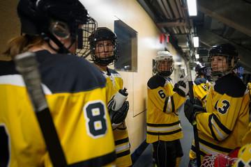 Womens ice hockey team talking outside locker room