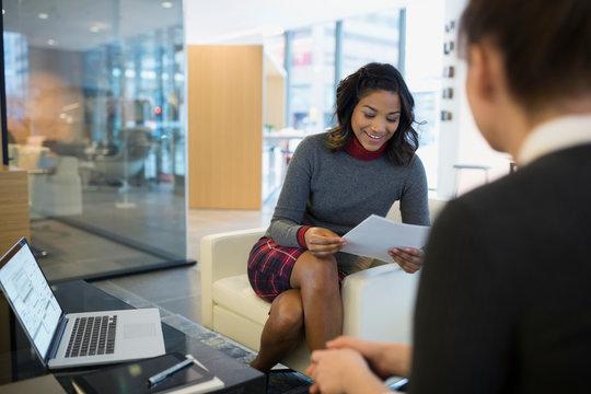 Businesswomen reviewing paperwork in office lobby