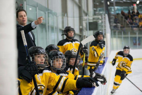 Womens ice hockey team and coach watching sideline