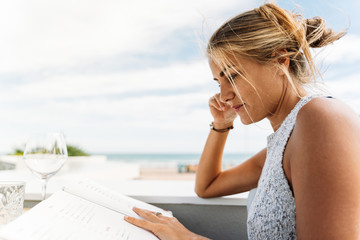 beautiful young girl looking at the menu in a restaurant, during a sunny day outdoors