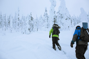 Men snowshoeing with camping backpacks up snowy slope