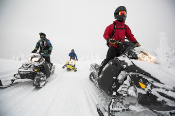 Men snowmobiling in remote snowy woods