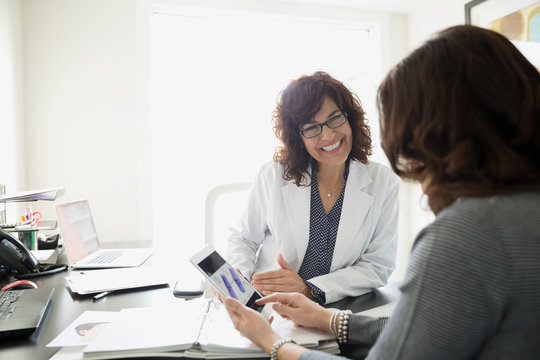 Smiling doctor with digital tablet consulting female patient