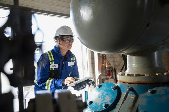 Female engineer digital tablet examining equipment gas plant