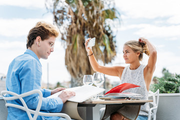 young girl looks at herself on her cell phone while they're on a date at the restaurant